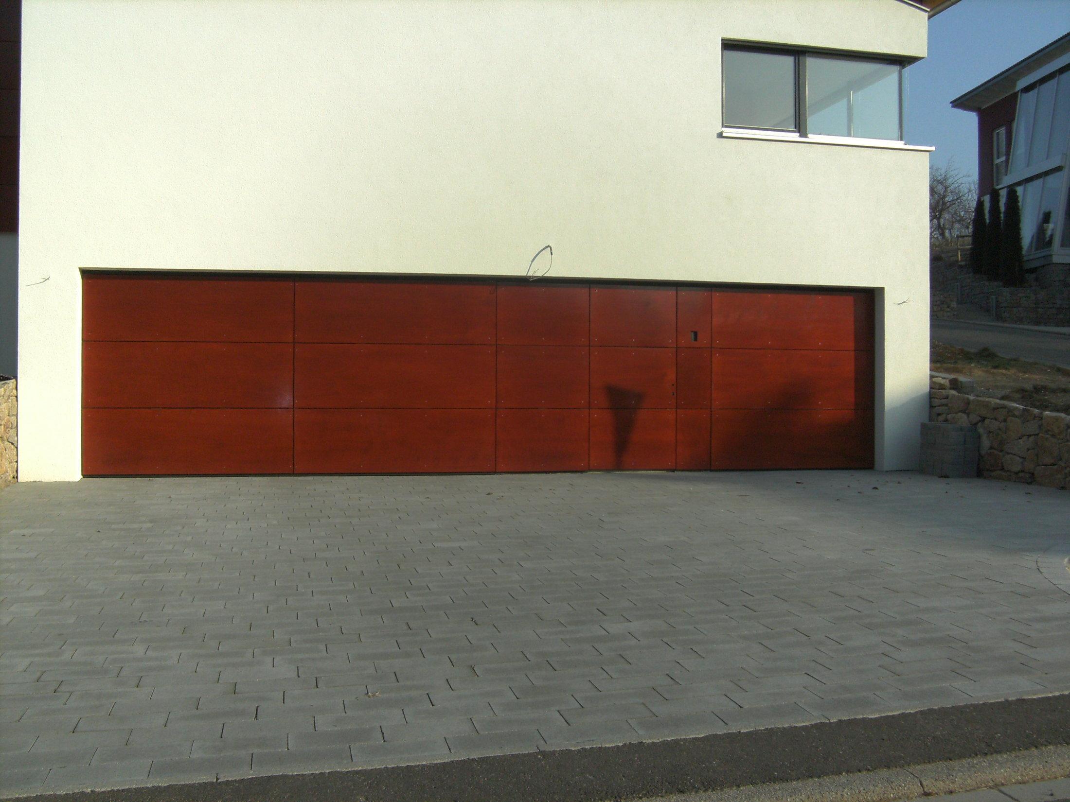 Flächenbündige Schwingtore mit Schlupftüre zwischen den Toren. Fläche mit lasierter Holzplatte verkleidet.