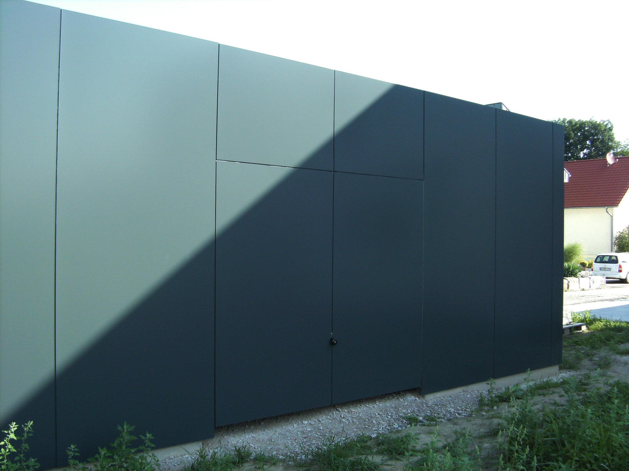 Flächenbündiges Schwingtor mit Fassadenplatten verkleidet