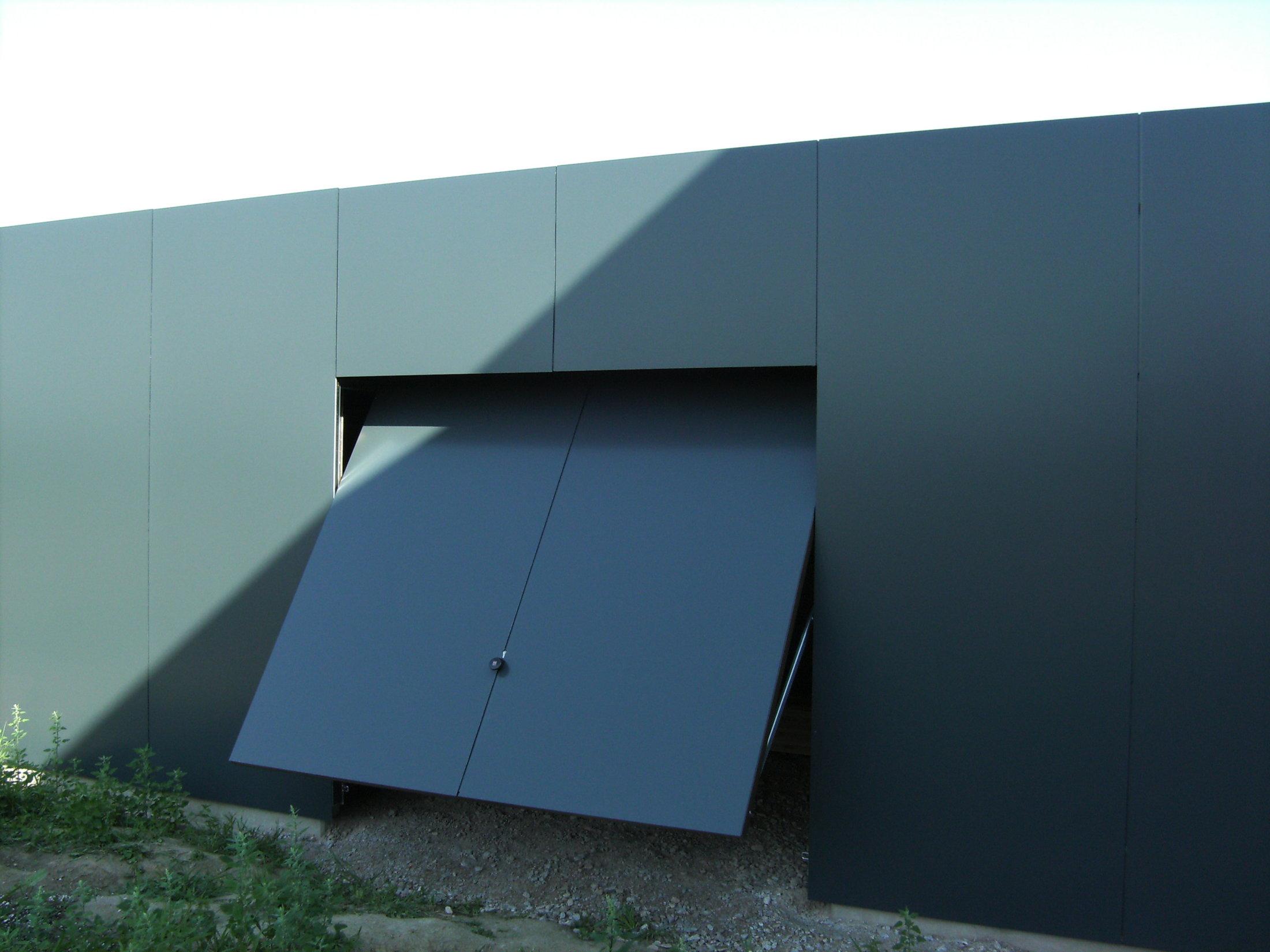 Flächenbündiges Schwingtor mit Fassadenplatten verkleidet - öffnend
