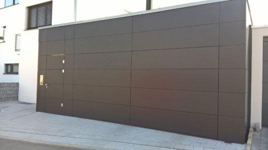 Flächenbündiges Sektionaltor und Nebentüre mit Trespa-Platten