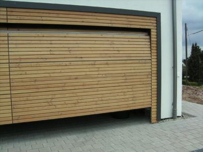 Flächenbündiges Sektionaltor mit seitlichen Blenden und fester Sturzverkleidung mit Rautenprofil Pinus Rombo verschalt - öffnend